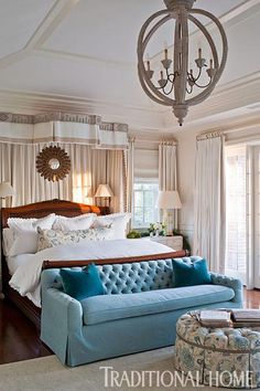 Adding a jolt of color to the serene master bedroom is a tufted blue sofa. - Traditional Home ® / photo: Michael Garland / Design: Emily Sulllivan