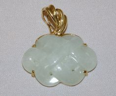 While some who view this carved Jadeite may see a Celtic knot, it is important to realize that the mystic knot is a very ancient motif for Chinese jewelry. This beautiful piece measures one inch long and a bit over 3/4 inches wide. The jadeite is transluscent and pierced at the junctures of the knots. The mounting is 14KT yellow gold and the bail is constructed so that in addition to wearing this as a pendant, the bail also snaps open to function as an enhancer for a string of pearls…