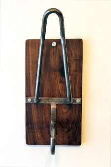 This sissy bar-inspired motorcycle helmet rack/hook was designed by me* and is hand bent and welded from half-inch steel and mounted on a one inch thick piece of waxed walnut measuring 13 by 7 1/4 inches.  It easily mounts to any wall (make sure to mount into a stud for strength) with the included mounting hardware and can hold any motorcycle helmet.  *Patent Pending