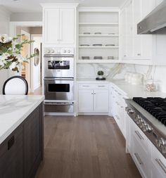 Amazing two-tone kitchen design with walnut kitchen island with white and black oval-back counter ...