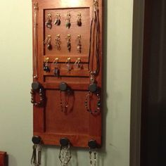 Repurposed door from entertainment center - now is a classy jewelry hanger.