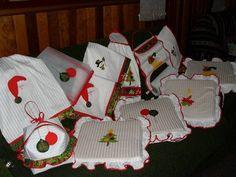 Bordado com aplicações de temas natalinos, papai noel, bolas, boneco de neve, meia, vela, árvores, etc... Ficou gracioso e delicado. As aplicações foram feitas para dar ênfase aos símbolos natalinos,  acabamento em vermelho, uma das cores que lembram o natal.  Neste kit foram feitos: toalha de mesa (o valor depende do tamanho e da quantidade de bordados), 2 toalha de fogão (R$ 33,00 cada), bate mão (R$ 30,00), pano de prato (R$ 22,00) , puxa saco (R$ 28,00), protetor de alimentos (R$ 21,00)…