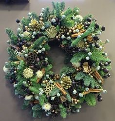 Silver and green Christmas wreath using pine cones, pine leaves, dried poppy heads, berries, eucalyptus flowers with cinnamon sticks by shelley Christmas Wreath Image, Christmas Door Wreaths, Handmade Christmas Decorations, Christmas Flowers, Green Christmas, Holiday Wreaths, Xmas Decorations, Christmas Crafts, Christmas Trends