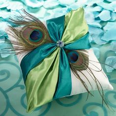 """Peacock Feather Ring Pillow  Measuring 7"""" x 7"""", this elegant ring pillow is covered in cream satin.  The front is decorated with a green and teal satin sash, two peacock feathers and a rhinestone ornament.  The ornament combines light blue rhinestones with one central dark blue rhinestone and a series of tiny green rhinestones."""
