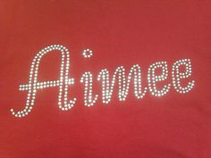 Aimee written in the Ballroom font and in the clear rhinestones to contrast against the red of the hoodie. We can do this name and any other in a variety of fonts/colours and apply it to a range of garments. For more info, please visit our website or give us a call!