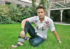 esta imagen nos muestra al actor Michel Brown sentado en un jardin muy tranquilo este actor es muy conocido por su actuacion en la telenovela Pasion De Gavilanes