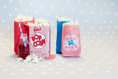 Decoración de fiestas. Bolsas de papel y cajitas de cartón Popcorn. Botellita de cristal y pajita de rayas azules y rojas.