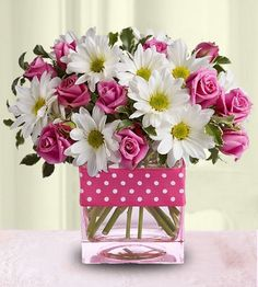 Pink miniature roses and white daisies have never been so festive as they are here collared with polka dot ribbon.