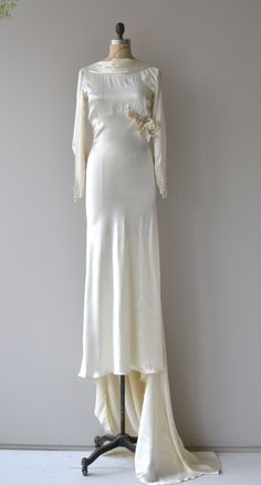 Vintage 1930s ivory silk satin wedding gown with luxurious weight, draped neckline, bias cut, long sleeves with long line of fabric buttons from the wrist, large silk flower and leaf decoration at one side, long extending train and side snap closures.