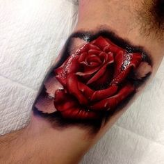 Vibrant red rose tattoo with black shadowing