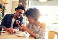 Friends in cafe using mobile phone by jacoblund. Portrait of happy young man and woman sitting together at a restaurant and looking at a mobile phone. Young friends l...