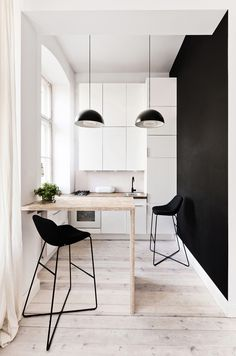 White walls and cabinets, blonde wood floors and table, with black accents create a stylish compact space.