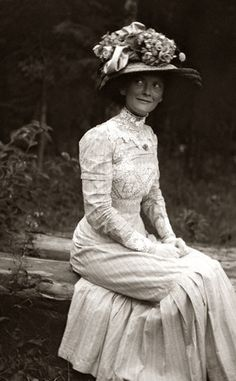 June 1900 - I love love love this picture so much.  From the amazing inlaid lace work, to the piles of things on her hat, right down to the humorous look on her face!