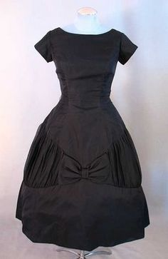 1950s Black silk organza layered over taffeta with a bell shaped skirt, ruching, and big bows.