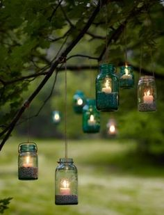Hang mason jars from a tree with rope and place some pea gravel and a mall candle to create a magical outdoor mood