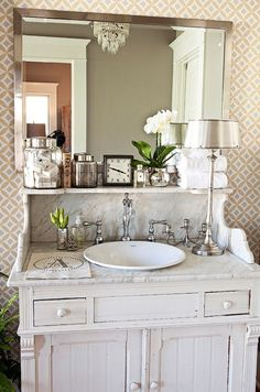 bathroom inspiration - pair up a tatty bit of furniture with silver accents, pattern wallpaper, fresh flowers and aristocratic hints (see the monogram on the towel). Beauty in contrasts.