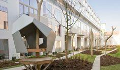 Une cour intérieure de diverses habitations qui intègre très bien les déplacements, le jardin, les zones de repos et les espaces de jeux pour les plus peti
