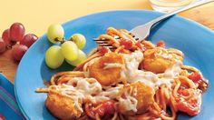 Chicken nuggets rest on a bed of spaghetti and pasta sauce in this tasty and hearty feast.