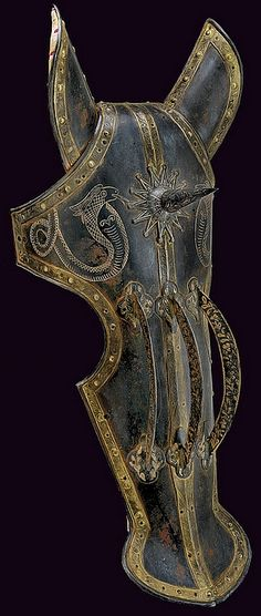 Indo-Persian chaffron (armor for a horses head), 19th Century, blued iron, with a cusp and three arched mounts, the border decorated by a gilt plaque engraved with floral motifs, at the upper part two gold-inlaid engravings depicting cobras; with ear covers, complete with inside stuffing, 68 cm.