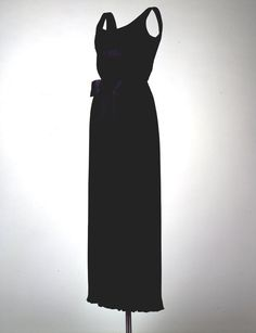 """Black Evening Dress Maker: Oleg Cassini (American, b. France, 1913-2006) Date(s) of Materials: 1961 Place Made: United States Medium: Silk satin Dimensions: 50 1/2"""" center back Description: An evening dress in black Fortuny-pleated silk satin with a satin bow at the waist. Historical Note: This dress was worn by Jacqueline Kennedy to the state dinner honoring President Romulo Betancourt of Venezuela, the White House, Washington, DC, February 19, 1963."""
