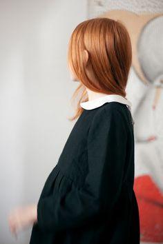 Black dress, white collar, red hair.