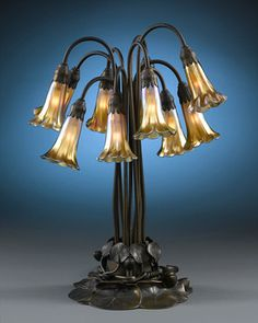 Tiffany Bronze and Favrile Lily Table Lamp - each pendant with a later gold iridescent shade, segmented tripart standard joined to circular ribbed base marked Tiffany Studios New York