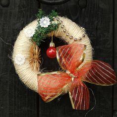 Věneček vánoční Vánoční dekorace na dveře, nebo na okno. Věneček je vyrobený ze sisalového provázku, ozdobený aplikacemi laděnými do červena, hvědičkou ze slámy, červeno zlatou mašlí a krajkovými vločkami. Průměr věnečku je 17 cm.
