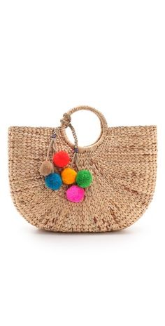 JADEtribe Large Beach Basket Tote. This structured straw tote is styled with cheerful curves and playful pom-poms, and has a colorful knit inset at the drawstring top to keep valuables secure at the beach.
