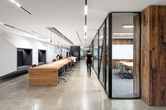 Uber SF headquarter office, San Francisco, CA. Custom hickory worktables in a corridor run parallel to an enclosure share by conference and training room.