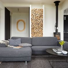 Modern living room with grey sofas and wood pile