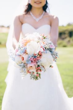 After an outdoor ceremony, the wedding continued at a breathtaking reception with tall, oversized centerpieces of beautiful summer floral arrangements.