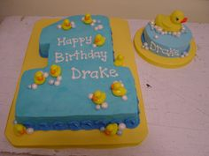 11x15 sheet cake cut to shape of 1.  Plastic duck cupcake picks were inserted on sheet cake (some of the pick stems wre removed).  Fondant bubbles/balls rolled in luster dust (not child safe since he tried to eat them immediately).  MMF covered board with grossgrain ribbon edge.  Smash cake has large rubber duckie from craft store.  This cake was inspired by other CC posts, thank you.