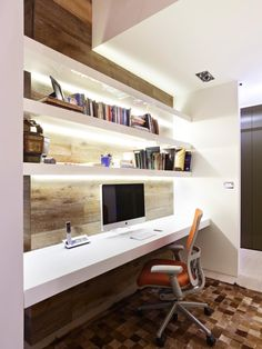This built-in home office features four levels of floating white shelves with the bottom shelf serving as the work space.