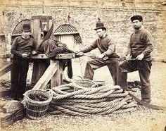 Three fishermen standing by a capstan on Brighton beach, English, c. 1860's. The man on the left of the camera holds a knife and a section of netting. The two men on the right hold a rope that is fixed to the capstan.