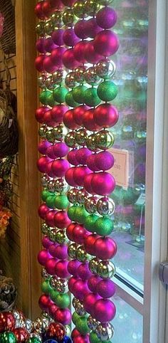 Christmas window treatment - get cheap ornaments at the dollar store, hang on fishing wire, knotting around the loop on each one, and then attach to a tension rod to display in window.