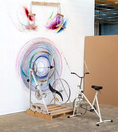 The spinning front wheel of the bike powers a special apparatus that draws circles on the surface using colored markers.