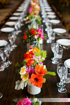 Vibrant Florals down a long wooden table. Chic and playful! Holly Flora, Callaway Gable, and Planning/Design by Amber Evnets