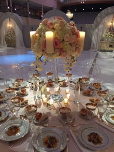 Elaborate flower ball featuring blousy white hydrangea, roses in creamy and pink tones, and stately phaleanopsis orchids rise above guest tables on elegant crystal candelabras surrounded by pillar candles and votive candlelight.