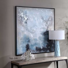 This modern, abstract painting features a crackle-texture finish that is awash in shades of ivory, deep blue, and charcoal. The canvas is completed with a black gallery frame. Designed by Carolyn Kinder International.