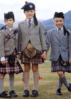 Three young whipper snappers in various stages of out growing their kilts and jackets!