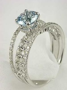 Antique style aquamarine engagement ring - wow...The 18k white gold band of this engagement ring is split into four rows of diamond strips. The eighty-two round full cut diamonds that accent these strips total 0.70 carats. The quartet of diamond rows join together at the center with a round faceted mixed cut aquamarine. From Mark Silverstein's Gossamer Collection.  Available for $2995 at topazery.com