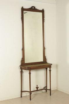 Consolle con specchio in stile Neoclassico retta da gambe troncoconiche con intaglio elicoidale raccordate da crociera. Specchiera con specchio bisellato. Intagliata con motivi floreali e geometrici.