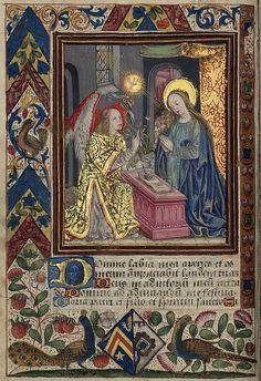 """L'Annonciation. Dans sa maison (en arrière plan la chambre à coucher et le lit), la Vierge, sous un baldaquin, agenouillée et les mains jointes en signe d'humilité, médite sur un livre (missel ou livre d'heures) posé sur un coffre prie-Dieu rose, sur lequel se trouve également un vase avec trois grands lys, symbolisant la triple virginité de Marie : """"ante partum, in partu, post partum"""". L'archange Gabriel est venu apporter la parole divine : """"Ave Maria, gratia plena"""". circa 1510"""