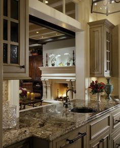 Heavy countertop with lovely detailed cabinets and an opening to the living area #houses #mansions #kitchens