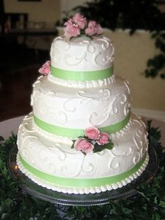 Traditional white cake with green ribbons and pink roses