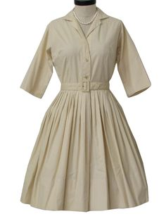 Late 50s -Lady Manhattan- Womens cream background cotton, mid length, short sleeve shirt dress with button front closure, modest v-neckline with thin notched fold over collar and optional roll back half sleeve styling. Dress has darted bust, inverted flat pleat back for ease in fit and mid waist seaming with matching belt that falls to full tight box pleated skirt. Really a fantastic shirt style day dress in awesome vintage condition!