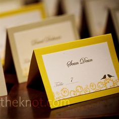 Laura went DIY with her escort cards. The eggshell-white cards, printed in brown with each guest's table number and the lovebird motif, were attached to yellow tented card stock.