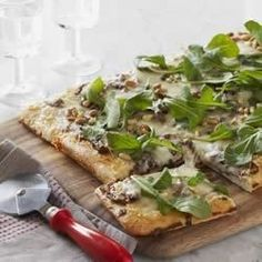 Create your own gourmet pizza topped with caramelized onions, fresh rosemary, arugula, and pine nuts on a cheesy, homemade crust.