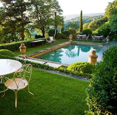 La Piscine - poolside decorating chic French outdoor garden setting beside a pool with finials sculpture urns france luxury summer
