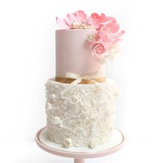 Floral baby shower cake  individual flowers on the bottom tier and adorned with pink florals topped with a baby figurine